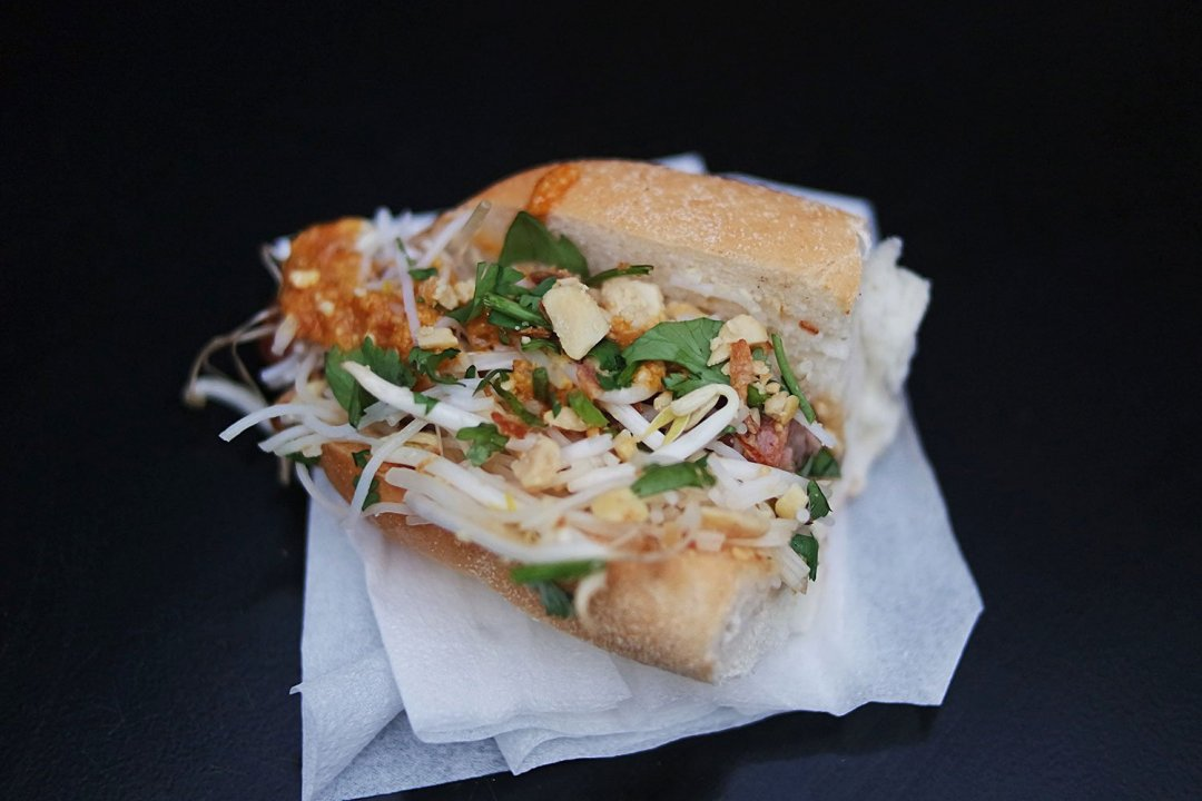 Pork sausage hot dog with pad thai seasoning, peanuts, coriander and fresh bean sprouts