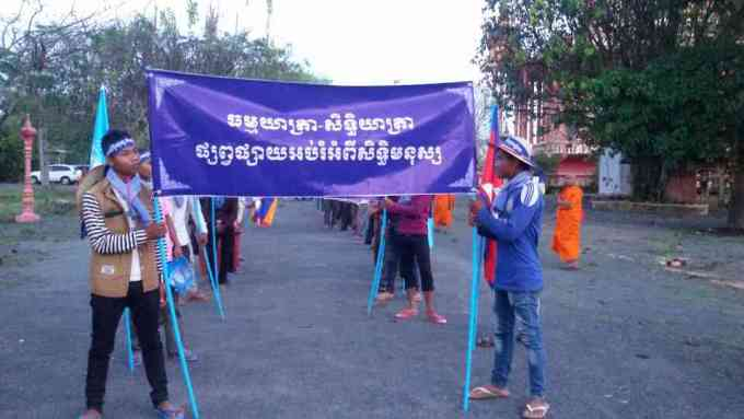 """Along Road 4, participants hold up a banner that reads """"March for Human Rights"""""""