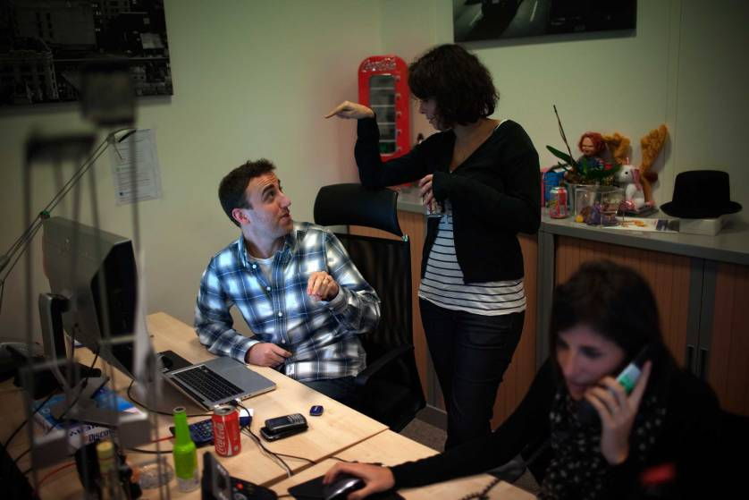 Employees chat at a desk inside the offices of Facebook in Paris, France on Nov. 29, 2010.