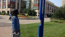 Discover the World of Communication student Naima Fonrose from Laurel, Maryland observes a blue phone emergency system on American University's campus. Photo by Emily Boyle