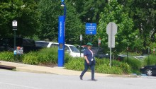 An American University staffer walks by an emergency tower on campus. Photo