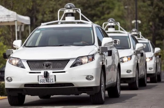 A line of Lexus SUVs equipped with Google self-driving sensors await test riders during a media preview of Google's prototype autonomous vehicles in Mountain View, California