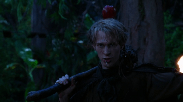 a screencap of felix (played by parker croft) with an apple on his head