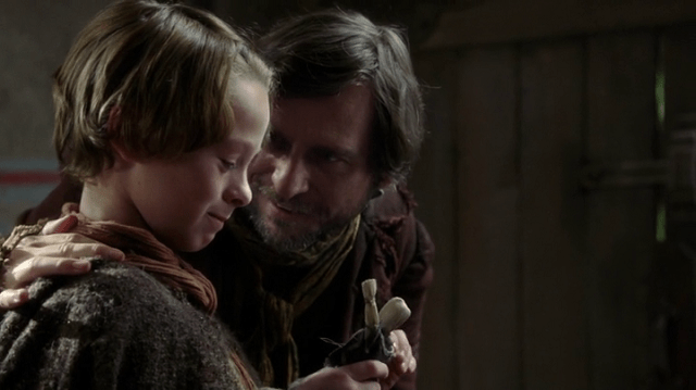 a screencap of rumpelstiltskin's father (played by stephen lord) giving a young rumpelstiltskin (played by wyatt oleff) a creepy doll