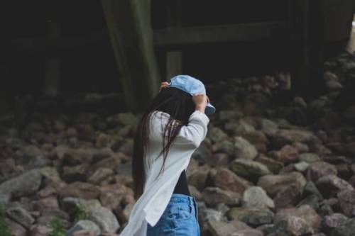 帽子に手を当てる女の人
