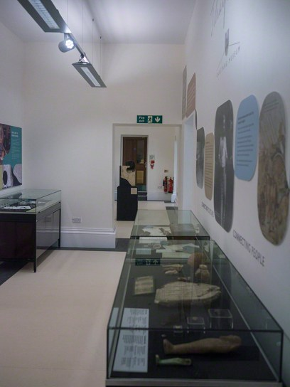 Looking down a gallery with photos and information panels on the wall and three glass cases with artefacts in them