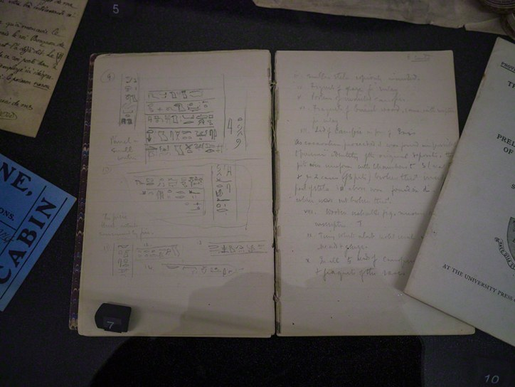 A lined notebook with hand-copied hieroglyphs and writing in a grey ink