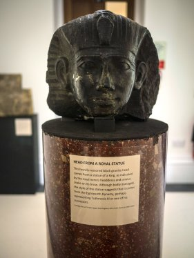 A head from a statue carved in black granite. The head is of a king, wearing the nemes headdress with a uraeus on the front