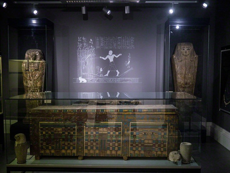 Looking into a gallery, with a large rectangular coffin in the foreground, two anthropoid coffin lids behind, flanking the wall mural of a man hunting in marshes