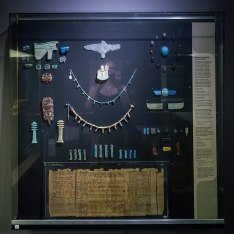 A case of jewelry and amulets, including bead necklaces, wedjat-eyes, scarab amulets, djed-pillars and a page from the Amduat (black ink on papyrus)