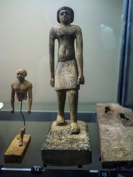 A small statue of a man wearing a kilt standing with his left foot forward. some detail such as collar and edging on the kilt has been added in black ink