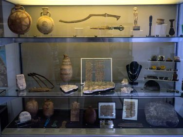 A glass-fronted case with three shelves of artefacts, including a kopesh sword, texts on papyrus, bes-jars and ceramic containers