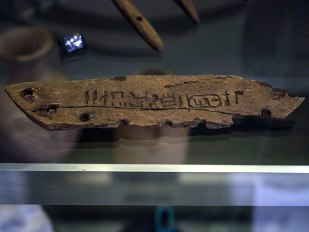 A small piece of wood in the shape of a rocker (semi-circular) with a line of hieroglyphs inscribed across the centre