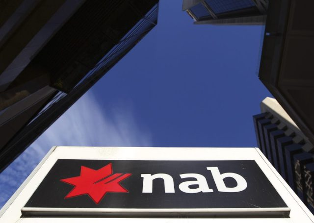 A National Australia Bank logo is displayed in bright sun while adjacent building sit in shade in Sydney, Australia, Thursday, May 10, 2012. National Australia Bank, one of the country's largest lenders, reported a 15.5 percent drop in first-half net profits on Thursday, hurt by the poor performance of its U.K. operations. (AP Photo/Rick Rycroft)