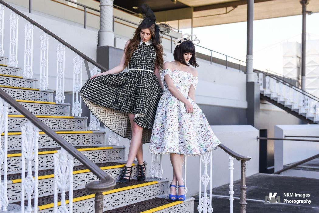 Mel wears Liza Emanuele 'Bella' dress in black, Katya Komarova 'The Bow' headpiece and ______ 'Helium' shoes in black. Kristen wears Liza Emanuele 'Lucy' dress, Katya Komarova 'Lace Headband 2' and ______ 'Heather' shoes in blue.