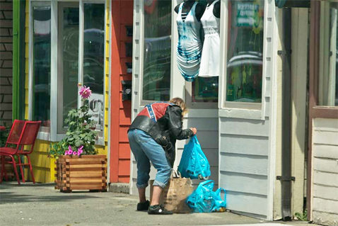 A woman rebags food items in front of a clothing store.