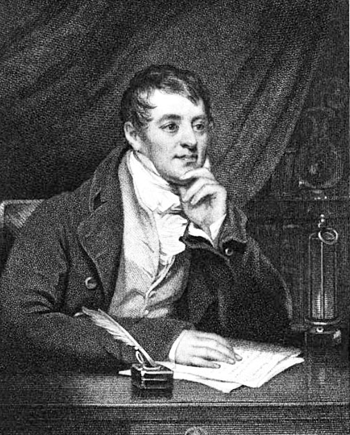 Regency man at desk with paper and a quill pen in an ink pot