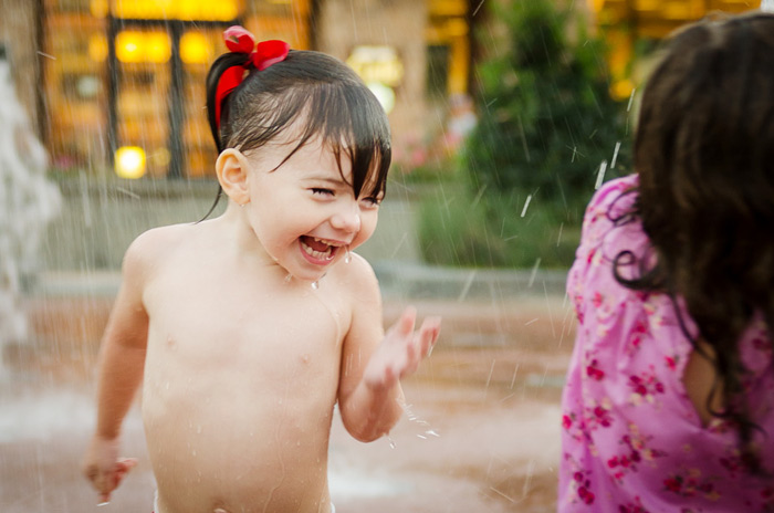 Chloe laughing and playing in the fountains