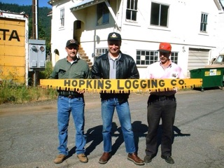 In 2003, I traveled to Greeville. Here, my high school friends, Mike Knadler on left, and John Hunter on right, pose with the Hopkins Logging Company logo crosscut saw that once hung on the Hopkins Logging Company office building in Greenville. John secured it from a garage sale, saved it, and gave it to me years later. I was astonished when I met up with the old saw again.