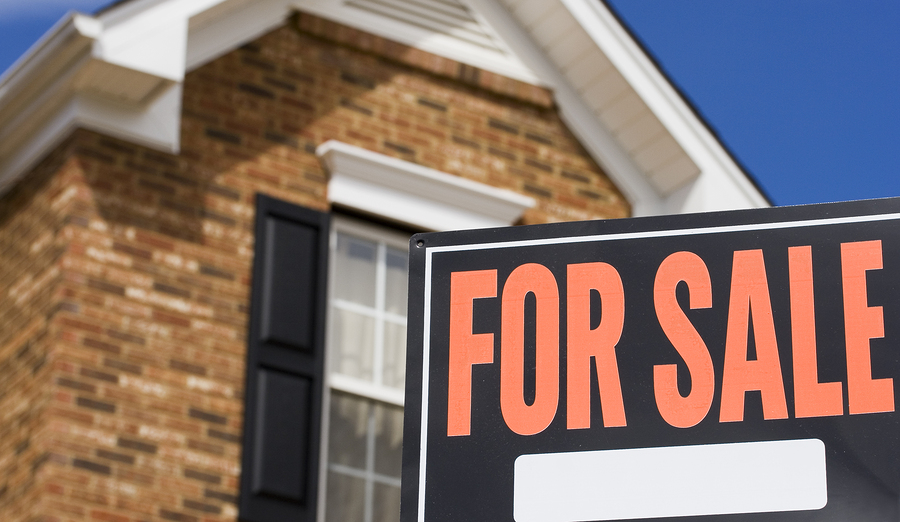 Home for sale - a sign in front of a brick house