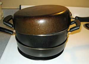 Image of Dutch oven with cover and skillet on top