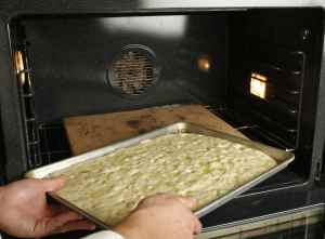 Placing the pan on the stone in the oven during the focaccia step-by-step process. Although its cousin, pizza, can stand in for a meal, focaccia is more of a snack, or at most an appetizer. In Italy, it's a popular walking-around food. Also, though cold pizza may have a certain raffish charm, focaccia really needs to be eaten when it's hot to be at its best. (Glenn Koenig/Los Angeles Times/MCT)