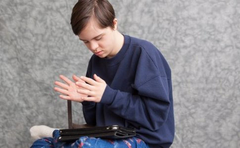 a boy with autism and down's syndrome clapping his hands as he plays with a tablet device
