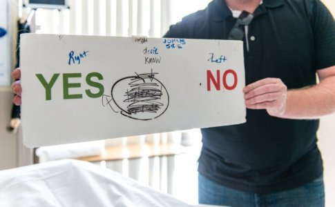 Jeremy Wilson, 40, communicates with his father using a makeshift board at St. John's Pleasant Valley Hospital in Camarillo, Calif., on Wednesday, February 24, 2016. His father, John Wilson, can't speak but can communicate using his eyes.  (Heidi de Marco/KHN)