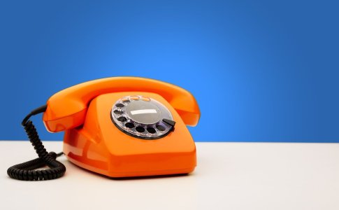 an orange rotary phone on a blue background. trying to arrange for therapy results in endless phone calls...and little help