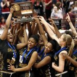 DeLaSalle High School basketball players, including junior guards Allina Starr, left, and Joi Jones (10) hoist the state Class AAA championship trophy following their 65-45 win over Richfield in the finals March 17 at Target Center in Minneapolis. The Islanders, who finished the season with a record of 28-3, successfully defended their state title. Last year, they defeated Hill-Murray in the championship game.  (Dave Hrbacek / The Catholic Spirit)
