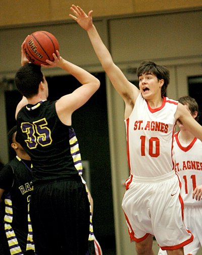Junior center Jack Fossand of St. Agnes High School in St. Paul tries to block a shot by sophomore center Francis Delaney of Cretin-Derham Hall during first-round action of The Catholic Spirit Christmas Basketball Tournament Dec. 27 at the University of St. Thomas. Cretin-Derham Hall won the game, 74-59.