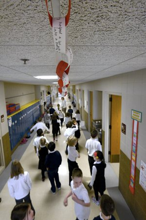 Kindergarten teacher Susie Smith walks her class through the hallway at All Saints School in Lakeville under a paper chain that hangs from the ceiling documenting the students' acts of peace and love. Jim Bovin / The Catholic Spirit