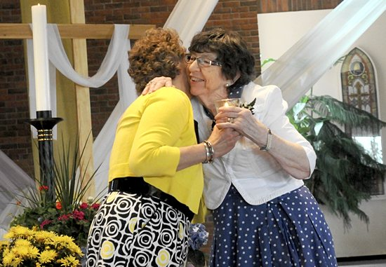 Past president of the Archdiocesan Council of Catholic Women, Rose Anne Hallgren, hugs new president Lucy Johnson during the installation of new officers at the organization's convention May 2 at Guardian Angels in Oakdale.