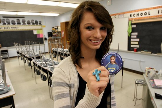 Kayla Trcka stands in the classroom at Most Holy Redeemer School in Montgomery where sixth-grader Mary Urtuzuastegui, pictured on button, attended school before she died in a car accident. Trcka, a senior at Tri-City United High School who was named homecoming queen, gave her crown to Mary's mother after the accident. Dave Hrbacek/The Catholic Spirit
