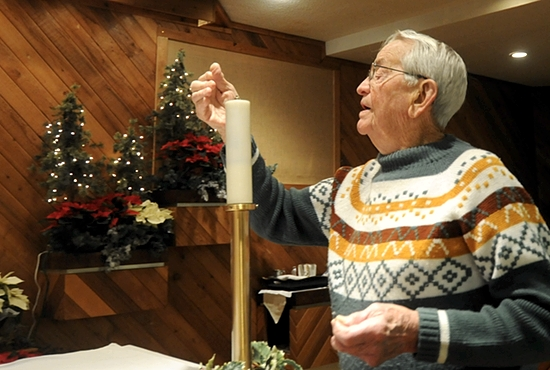 Len Lorence lights a candle for daily Mass Jan. 8 at St. John Vianney in South St. Paul. Dianne Towalski / The Catholic Spirit