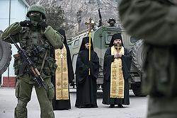 Orthodox clergymen pray near armed servicemen outside Ukrainian border guard post
