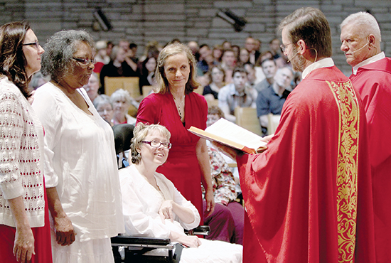 From left, Mary Johnson, Frances Fairchild, Pam Waltz, Kathy Gatto, Father Tim Norris and Deacon Tim Zinda stand before the congregation at  St. Paul in Ham Lake during Mass on Pentecost Sunday, June 8. Fairchild and Waltz were there to be received into the Church, with Johnson and Gatto serving as their sponsors.  Dave Hrbacek/The Catholic Spirit
