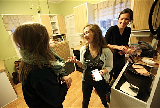 From left, Kaly Kohns, Lauren DeZelar and Jackie Meyer laugh as they prepare dinner in the kitchen of an SPO women's household near the University of Minnesota. DeZelar and Meyer live in the house, while Kohns is a frequent guest. Dave Hrbacek/The Catholic Spirit