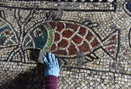 A student from the Jericho Mosaic Center cleans a mosaic in the Franciscan section of the Church of the Holy Sepulcher in the Old City of Jerusalem March 17. CNS photo/Debbie Hill