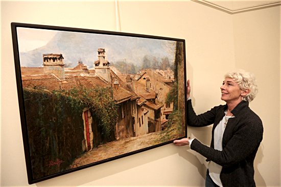 """Tennessee artist Anne Goetze hangs one of her pieces in the """"Pray to Love: The Annecy, France, Nun Series"""" in the John XXIII Gallery at the Basilica of St. Mary in Minneapolis. Photo by Dave Hrbacek/The Catholic Spirit"""
