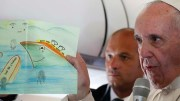 Pope Francis shows a drawing given by a child in a refugee camp as he answers questions from journalists aboard his April 16 flight from the Greek island of Lesbos to Rome. Journalists must not foment fear when covering issues or events such as forced migration due to war or famine, the pope said during a Sept. 22 audience with representatives of Italy's national association of journalists. (CNS photo/Paul Haring) See POPE-JOURNALISM Sept. 22, 2016.