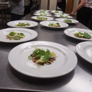 Salads being plated in the kitchen
