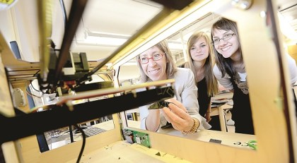 Left to right, Jan Baum, now director of 3D Maryland, and interns Sierra Turner and Jessica Searfino watch as a 3-D printer in the Object Lab at Towson University goes to work. (The Daily Record/Maximilian Franz)
