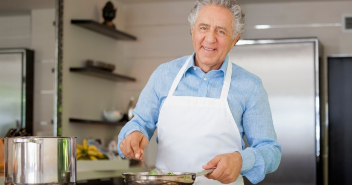 Older man in a kitchen wearing an apron and cooking at stove