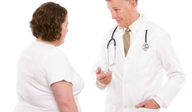 Physician in white lab coat speaking to middle aged obese woman