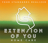 Outline of hand holding home on green and orange sunset background. Words Extension of You Home Care.