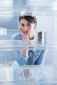 Woman looking into empty refrigerator, realizing her aging parents need care.