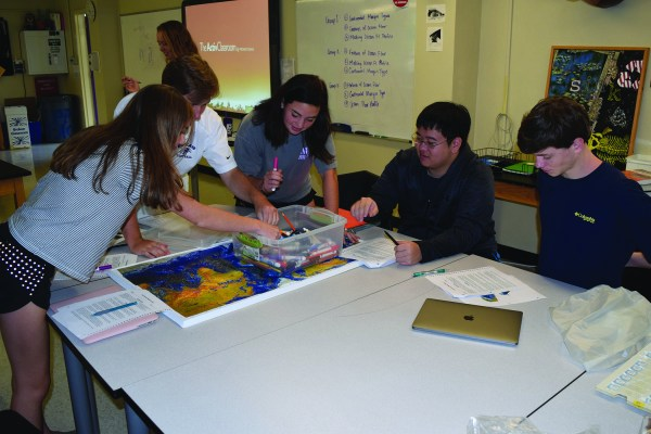 Seniors Allison Favaloro, Jack Tower, Belle Martire, David Liang, and Will Langford learn about the features of the sea floor on a topographical map in Marine Science. Photo by: Katherine Montgomery.