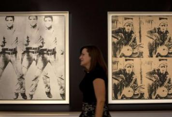 "A woman walks between ""Triple Elvis"" and ""Four Marlons"" by Warhol"
