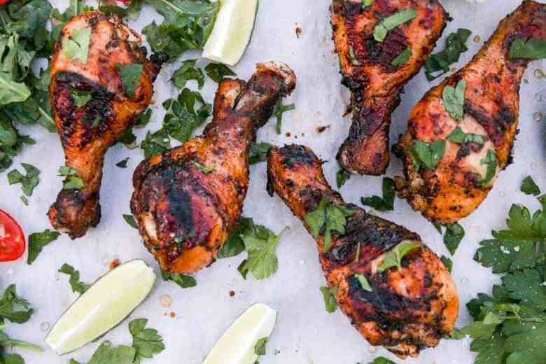 Four Grilled Chicken Drumsticks with lime wedges and scattered cilantro